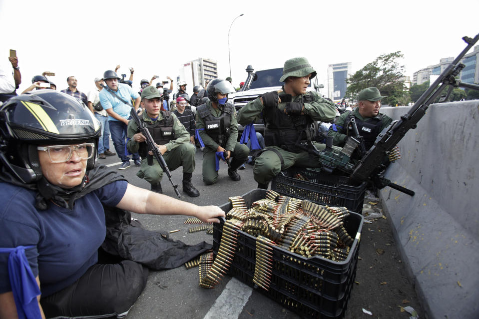 FILE - In this April 30, 2019 file photo, an anti-government protester sits by ammunition being used by rebel troops rising up against the government of Venezuela's President Nicolas Maduro as they all take cover on an overpass outside La Carlota military airbase where the rebel soldiers confront loyal troops inside the base in Caracas, Venezuela. Last April, as a military uprising roiled Venezuela, President Nicolás Maduro's socialist government ordered pay TV providers to immediately cease transmission of CNN and the BBC. DirecTV, which is wholly owned by AT&T, quickly obliged, yanking the two networks off the air. (AP Photo/Boris Vergara, File)