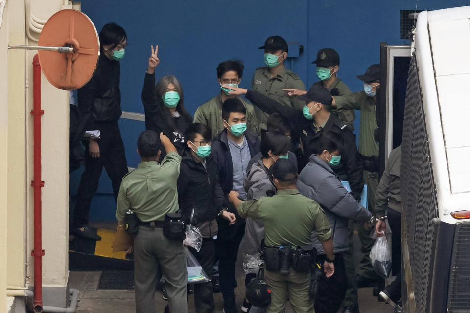 "Former lawmaker Leung Kwok-hung, known as ""Long Hair,"" second left, shows a victory sign and some of the 47 pro-democracy activists are escorted by Correctional Services officers to a prison van in Hong Kong, Thursday, March 4, 2021. A marathon court hearing for 47 pro-democracy activists in Hong Kong charged with conspiracy to commit subversion enters its fourth day on Thursday, as the court deliberates over whether the defendants will be granted bail. (AP Photo/Kin Cheung)"