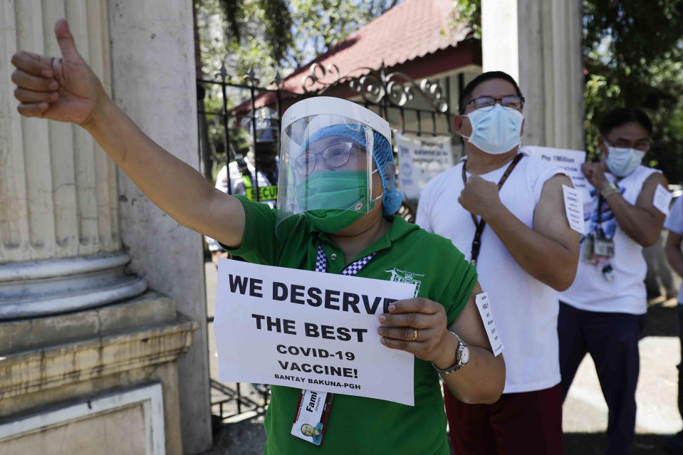 FILE - In this Friday, Feb. 26, 2021 file photo, a health worker wearing a face mask and shield holds a sign as she and others call on the government to give them a vaccine with the safest, highest efficacy and effectivity during a a protest outside the Philippine General Hospital in Manila, Philippines. The group is opposing a plan by the government to have health workers vaccinated with China's Sinovac. (AP Photo/Aaron Favila)