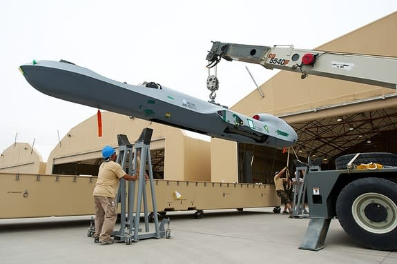 Workers unbox the fuselage of a Reaper drone at Kandahar Airfield in Afghanistan.