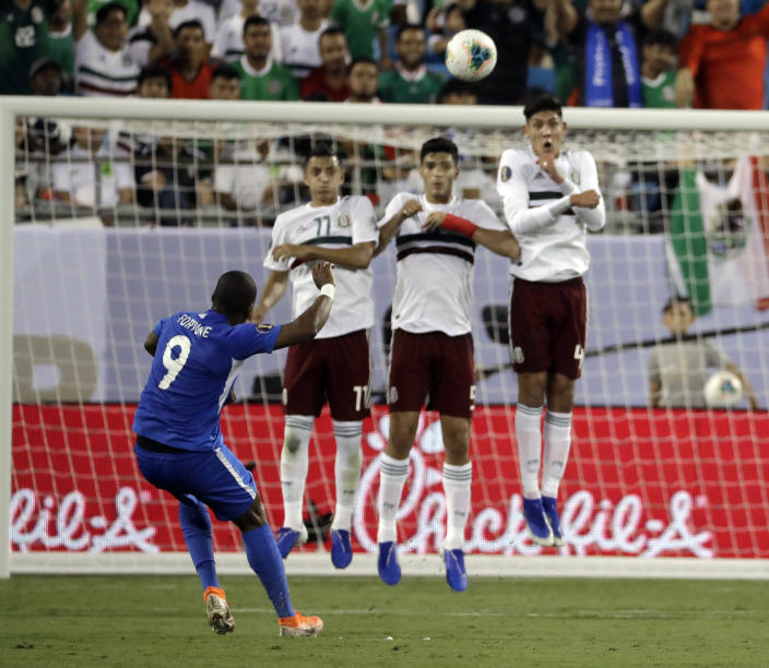 Martinique's Kevin Fortune (9) takes a free kick over Mexico players Roberto Alvarado (11), Diego Reyes (5) and Edson Alvarez (4) during the first half of a CONCACAF Golf Cup soccer match in Charlotte, N.C., Sunday, June 23, 2019. (AP Photo/Chuck Burton)