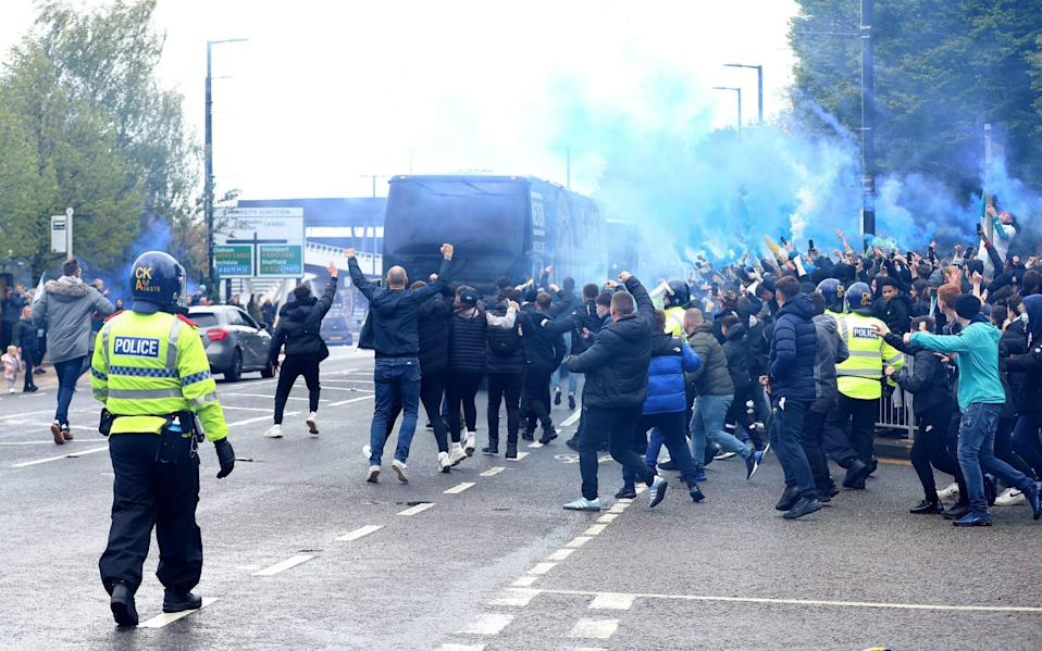 Fans run towards the Manchester City team bus as it arrives at the stadium prior to the Premier League match - PA