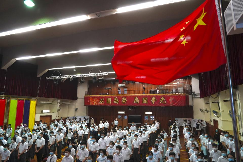 "Students attend a flag raising ceremony during the National Security Education Day at a secondary school, in Hong Kong, Thursday, April 15, 2021. Beijing's top official in Hong Kong on Thursday warned foreign forces not to interfere with the ""bottom line"" of national security in Hong Kong, threatening retaliation even amid ongoing tensions between China and Western powers. (AP Photo/Kin Cheung)"