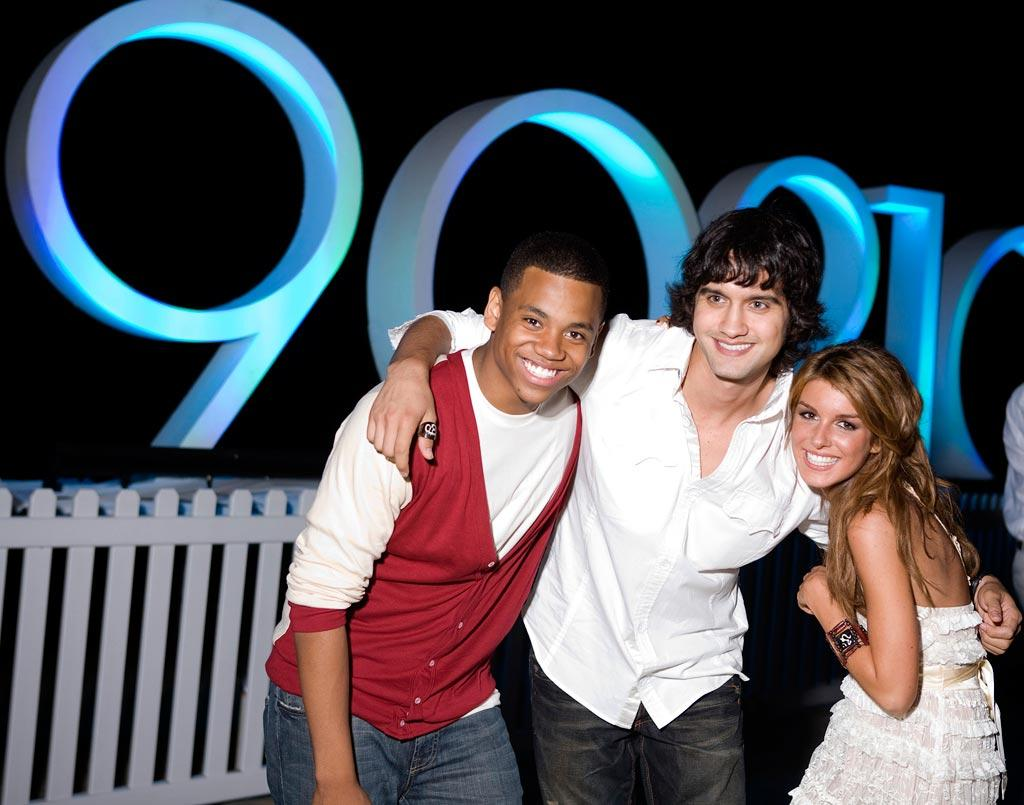 """Tristan Wilds, Michael Steger and Shenae Grimes pose in front of the fire pit at the <a href=""""/90210/show/43006"""">""""90210""""</a> Launch Party on Saturday, 8/23 in Malibu, California."""