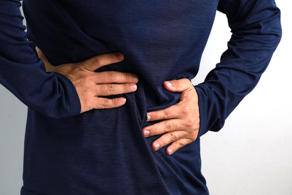 Midsection of mid adult man feels strong stomach pain. People, healthcare and medicine concept.