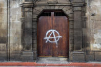 A painted anarchy symbol adorns a door of the Metropolitan Cathedral in Guatemala City, Sunday, Nov. 22, 2020. Protesters also broke into the building and set Congress partially on fire amid growing demonstrations against President Alejandro Giammattei and the legislature for approving a controversial budget that cut educational and health spending. (AP Photo/Moises Castillo)