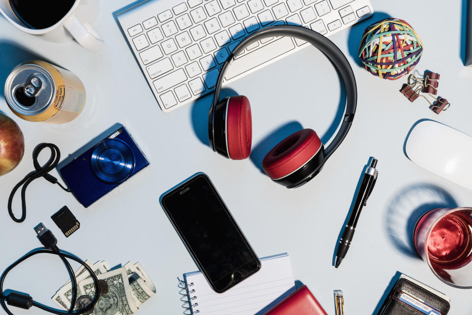 View form above headphones, smart phone, digital camera and office supplies on desk