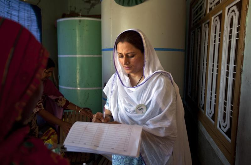 In this Monday, April 29, 2013, Ruksana Ali, an activist from the Association for Gender Awareness & Human Empowerment enlists  names of women for the upcoming elections in Mateela village near Sargodha, Pakistan. As the country gets set to vote in the upcoming nationwide election that will see a transfer of power from one civilian government to the next -- a first for Pakistan -- women still face an uphill battle to make their voices heard in the political process. (AP Photo/Rebecca Santana)