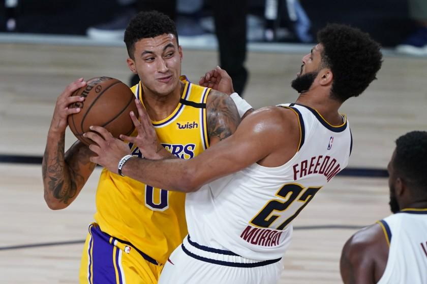 Los Angeles Lakers' Kyle Kuzma (0) drives to the basket against Denver Nuggets' Jamal Murray (27) during the second half of an NBA basketball game Monday, Aug. 10, 2020, in Lake Buena Vista, Fla. (AP Photo/Ashley Landis, Pool)