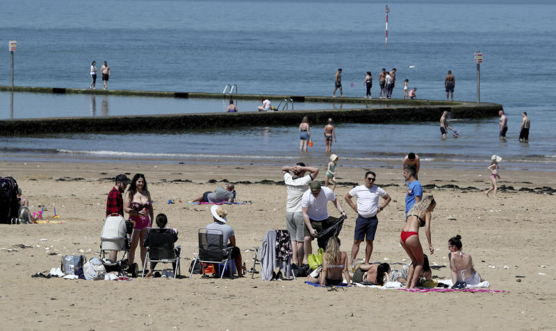 People settle to enjoy the good weather on the beach in Margate, Kent, after the introduction of measures to bring the country out of lockdown, in Margate, England, Tuesday May 19, 2020. (Gareth Fuller/PA via AP)