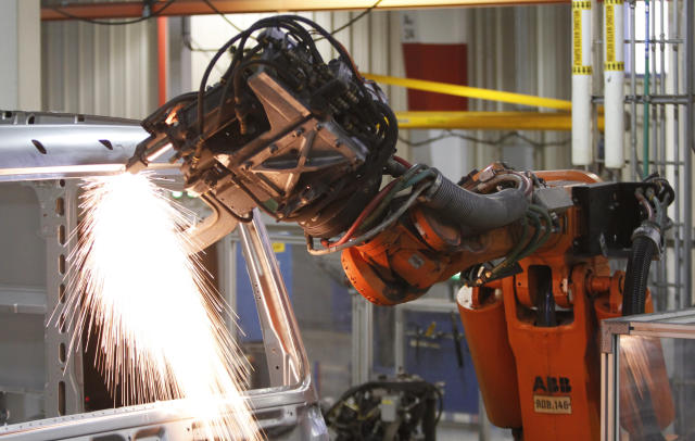 An industrial robot welds a car together. Source: AP