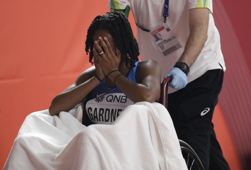 English Gardner, of the United States covers her face after getting injured in the women's 100 meter semifinal at the World Athletics Championships in Doha, Qatar, Sunday, Sept. 29, 2019. (AP Photo/Petr David Josek)