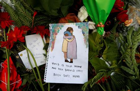 Flowers and signs are pictured at a memorial as a tribute to victims of the mosque attacks, near a police line outside Masjid Al Noor in Christchurch, New Zealand, March 17, 2019. REUTERS/Jorge Silva