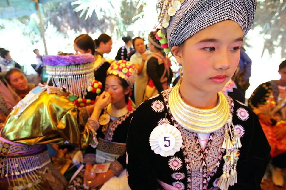 Contestants in a beauty pageant wait backstage during Hmong New Year celebrations Tuesday, Jan. 3, 2006, in Nong Hoi Mai village, north of Chiang Mai, Thailand. The Hmong, who trace their roots back to China, have large populations in Thailand, Myanmar, and Laos. (AP Photo/David Longstreath)