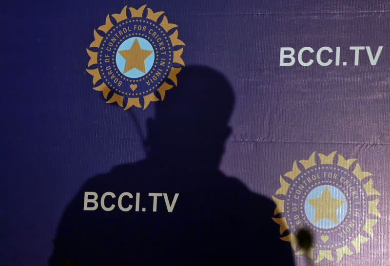 FILE PHOTO: The shadow of a man falls on a backdrop with the logo of the India's cricket board BCCI before the start of a news conference to announce its cricket team's coach, in Mumbai,