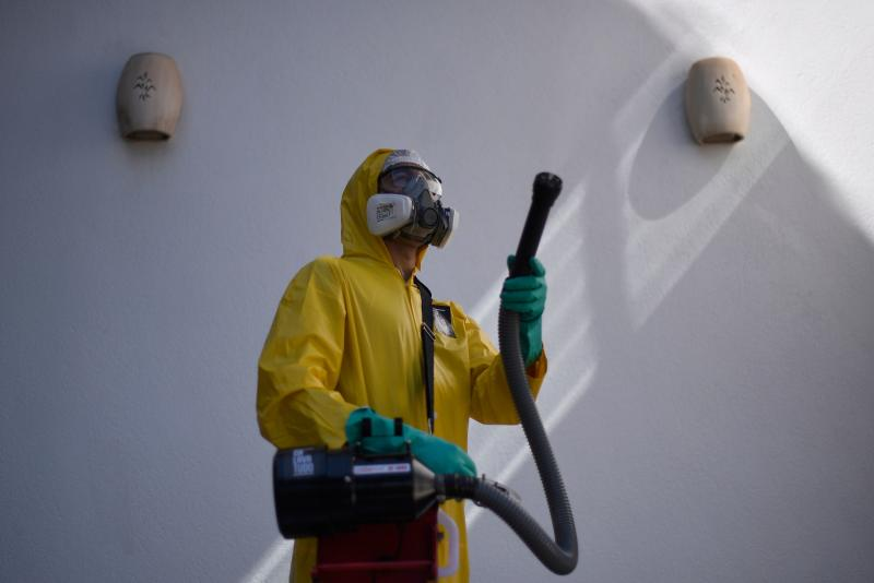 An employee of a private company sanitizes against the spread of the novel coronavirus COVID-19 at a house in Belo Horizonte, state of Minas Gerais, Brazil, on June 26, 2020. - The pandemic has killed at least 487,274 people worldwide since it surfaced in China late last year, according to an AFP tally at 1100 GMT on Friday, based on official sources, while Brazil, the hardest-hit country in Latin America, had close to 55,000 deaths. (Photo by Douglas MAGNO / AFP) (Photo by DOUGLAS MAGNO/AFP via Getty Images)