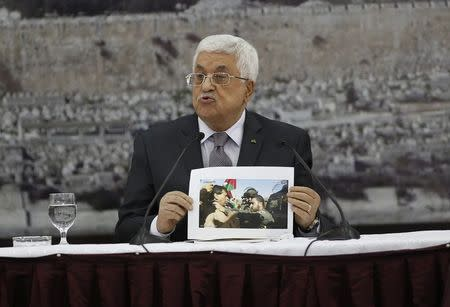 Palestinian President Mahmoud Abbas shows a picture of Palestinian minister Ziad Abu Ein as he is grabbed by an Israeli border policeman, during a meeting in Ramallah