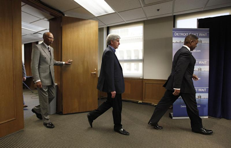 Detroit Mayor Dave Bing, from left, Gov. Rick Snyder and Kevyn Orr, arrive at a news conference in Detroit, Thursday, March 14, 2013. Snyder announced that he had chosen Orr, a partner in the Cleveland-based law and restructuring Jones Day firm, as Detroit's emergency manager. Snyder's already declared a financial emergency in Detroit, saying local officials lacked a plan to solve it. (AP Photo/Paul Sancya)