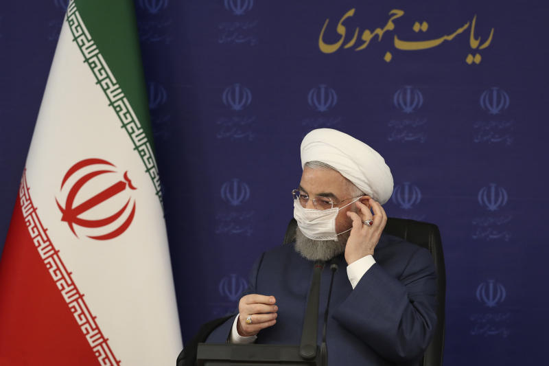 """In this photo released by the official website of the office of the Iranian Presidency, President Hassan Rouhani adjusts his face mask in a meeting of the national headquarters of the fight against the COVID-19, in Tehran, Iran, Saturday, July 18, 2020. He estimated as many as 25 million Iranians could have been infected with the coronavirus since the outbreak's beginning, citing an Iranian Health Ministry study that has so far not been made public, the state-run IRNA news agency reported. Writing in Farsi at top right reads, """"The Presidency."""" (Iranian Presidency Office via AP)"""