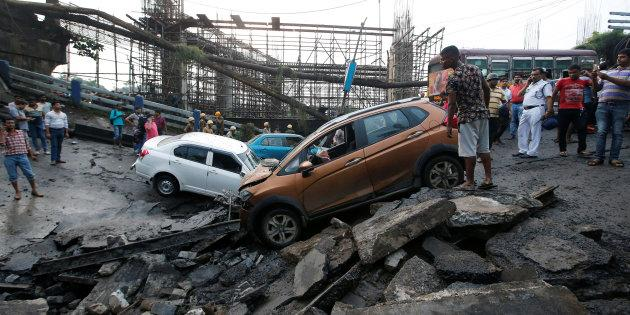 433c5d0bd6f People stand next to the wreckage of vehicles at the site of a bridge that  collapsed