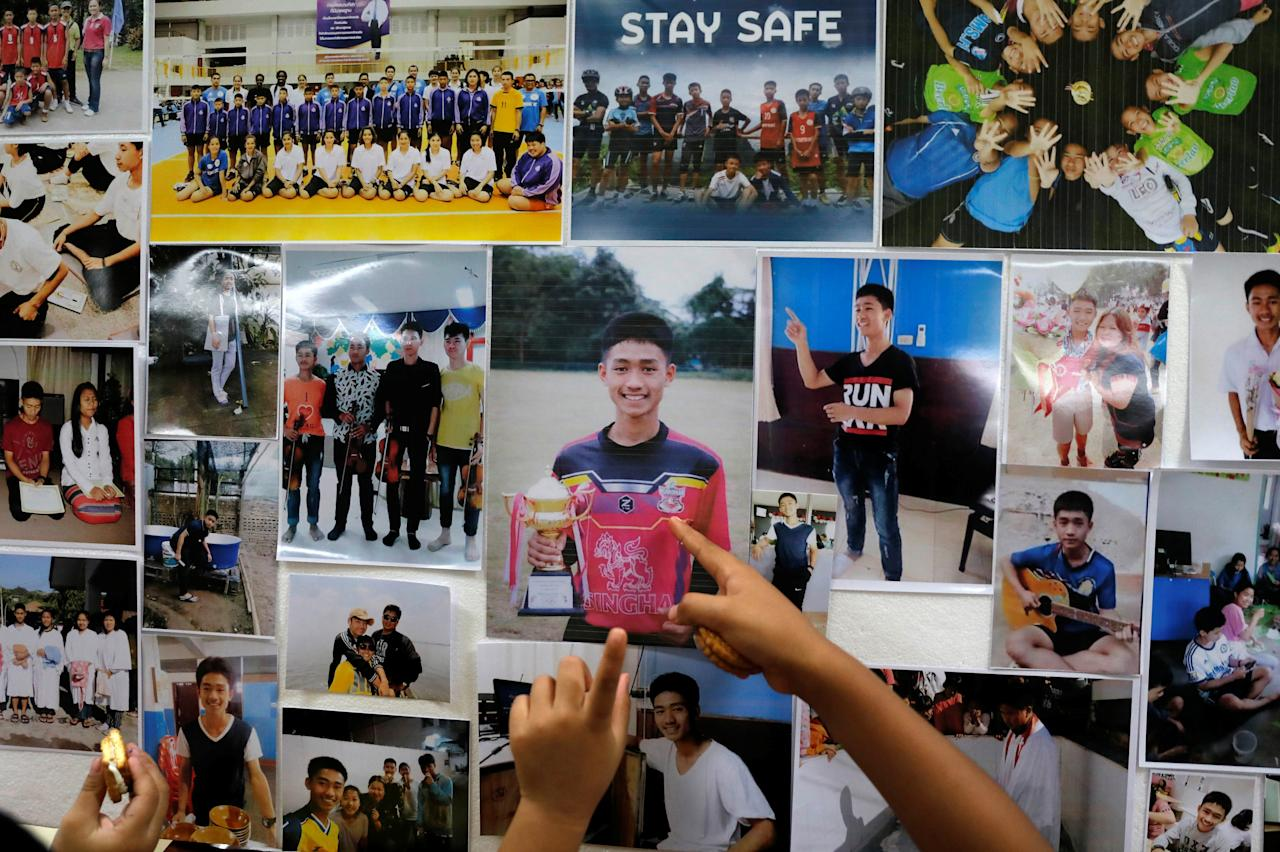 <p>Children look at pictures of students before relatives and friends pray for the 12 schoolboys and their soccer coach trapped inside a flooded cave, at Mesai Grace Church in the northern province of Chiang Rai, Thailand on Sunday (8 July). (PHOTO: Reuters) </p>