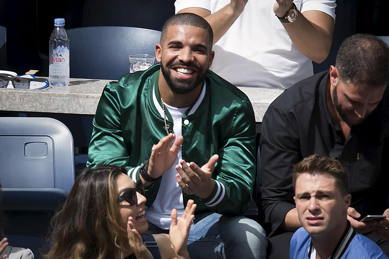 Musician Drake applauds as his image is displayed on the TV monitors during the Serena Williams, Roberta Vinci match at the U.S. Open Championships tennis tournament in New York, September 11, 2015. REUTERS/Carlo Allegri/File Photo