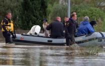 Rescue workers pulling a boat along, wade on a flooded street at San Gavino Monreale in Sardinia island November 18, 2013. REUTERS/Rosaspress