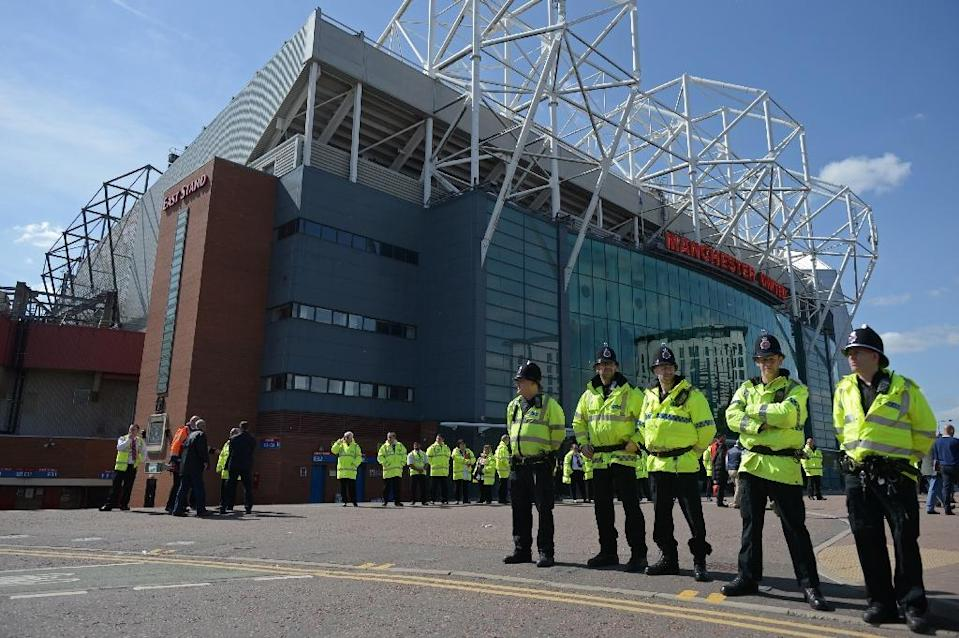 Police officers stand outside Old Trafford stadium in Manchester on May 15, 2016, after it was evacuated (AFP Photo/Oli Scarff)