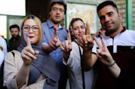 Iranians show their ink-stained fingers after casting their ballots in presidential elections at a polling station in southern Tehran on May 19, 2017 (AFP Photo/ATTA KENARE)