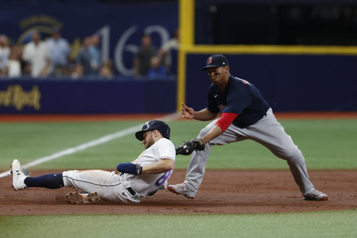 Tampa Bay Rays' Brandon Lowe beats the tag of Boston Red Sox third baseman Rafael Devers, advancing on a single by Ji-Man Choi during the third inning of a baseball game Saturday, July 31, 2021, in St. Petersburg, Fla. (AP Photo/Scott Audette)