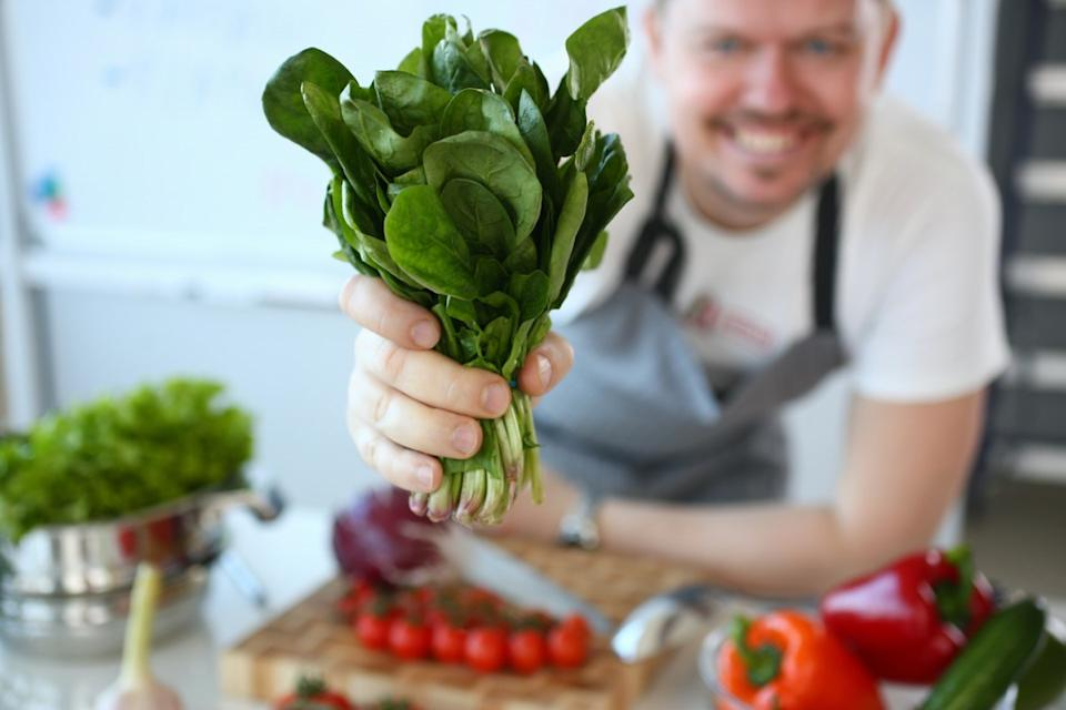 Man hold useful bunch of spinach in hand closeup on kitchen background