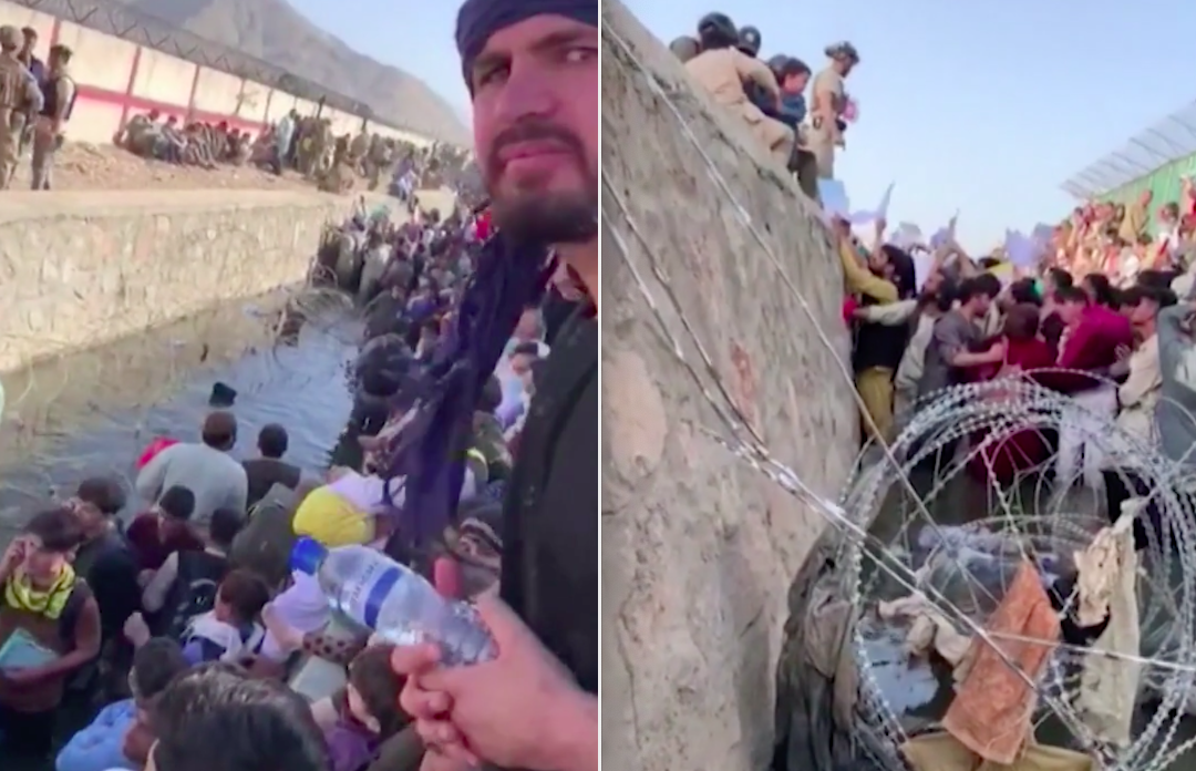 Afghans wade in water and between barbed wire as they wait outside Kabul airport.