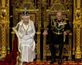 FILE - In this Wednesday, May 9, 2012 file photo, Britain's Queen Elizabeth II sits next to Prince Philip in the House of Lords as she waits to read the Queen's Speech to lawmakers in London. Buckingham Palace says Prince Philip, husband of Queen Elizabeth II, has died aged 99. (AP Photo/Alastair Grant, File)