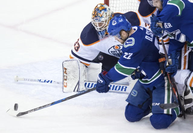 Vancouver Canucks left wing Daniel Sedin (22), of Sweden, takes a shot from his knees and is stopped by Edmonton Oilers goaltender Cam Talbot (33) during the second period of an NHL hockey game Thursday, March 29, 2018, in Vancouver, British Columbia. (Darryl Dyck/The Canadian Press via AP)