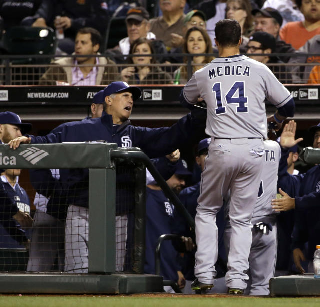 San Diego Padres' Tommy Medica (14) is greeted in the dugout after scoring on a double from Rene Rivera during the fourth inning of a baseball game against the San Francisco Giants on Monday, April 28, 2014, in San Francisco. (AP Photo/Marcio Jose Sanchez)