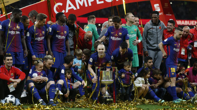 FC Barcelona's Andres Iniesta holds the trophy with teammates as they celebrate during an award ceremony after defeating Sevilla 5-0 in the Copa del Rey final soccer match at the Wanda Metropolitano stadium in Madrid, Spain, Saturday, April 21, 2018. (AP Photo/Francisco Seco)