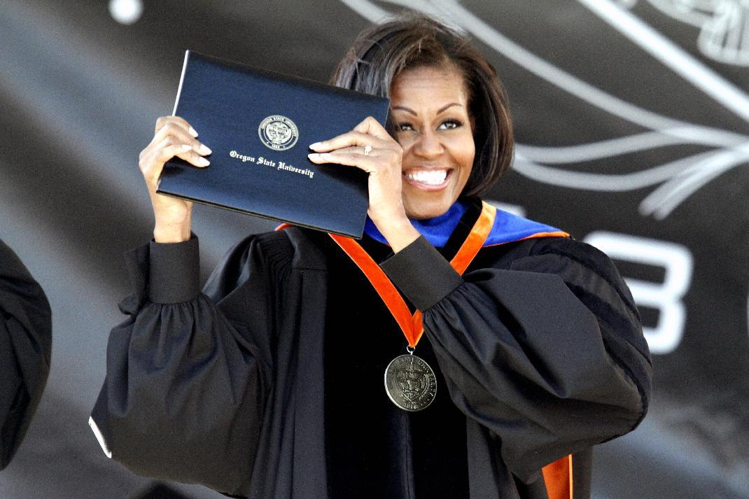 First Lady Michelle Obama holds up her diploma after receiving an honorary degree during the Oregon State University graduation ceremony in Corvallis, Ore., Sunday June 17, 2012. The First Lady gave the commencement address at Oregon State University, the school where her brother is the head basketball coach. (AP Photo/Don Ryan)