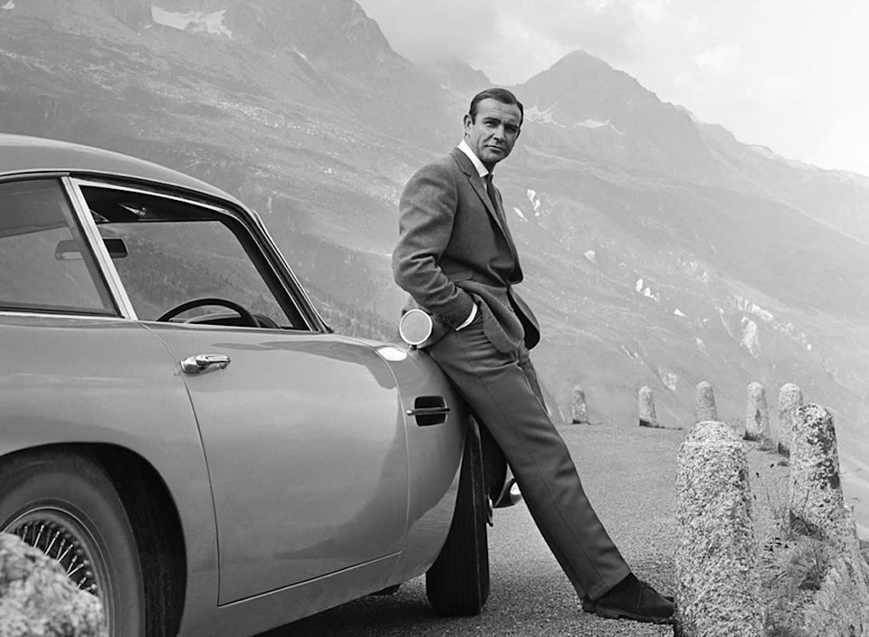 Sean Connery poses as James Bond next to his Aston Martin DB5 in a scene from 'Goldfinger'
