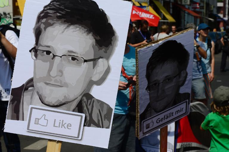 Demonstrators hold placards featuring an image of former US intelligence contractor Edward Snowden as they take part in a protest against the US National Security Agency in Berlin on July 27, 2013