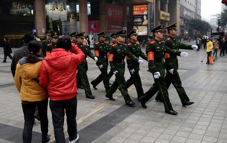 Chinese paramilitary police march through the shopping area of Chongqing,  February 3, 2013
