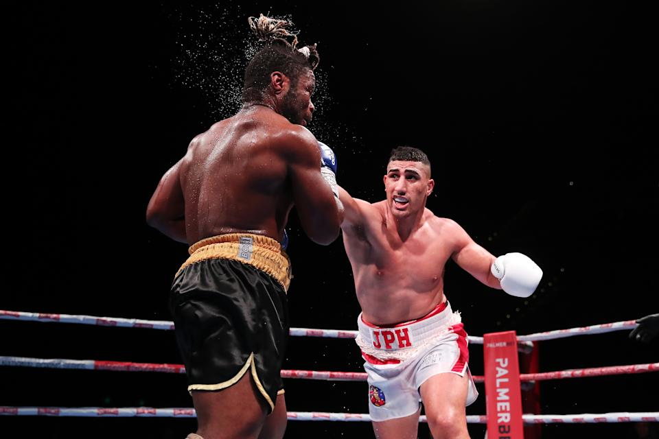 Justis Huni (pictured right) and Christian Tsoye (pictured left) exchange punches during the Australian Heavyweight bout.