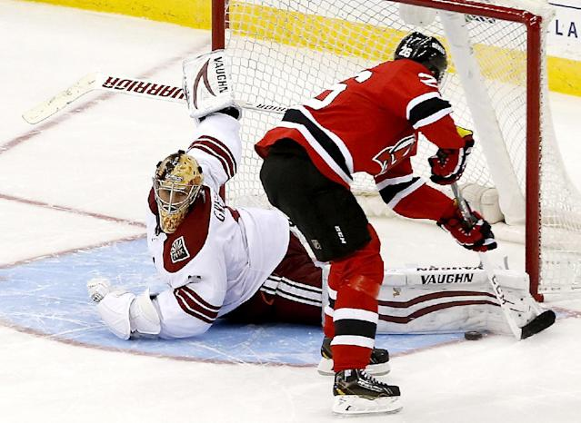 Phoenix Coyotes goalie Thomas Greiss, left, of Germany, blocks a shot by New Jersey Devils left wing Patrik Elias, of the Czech Republic, during a shootout in an NHL hockey game, Thursday, March 27, 2014, in Newark, N.J. The Coyotes won 3-2. (AP Photo/Julio Cortez)