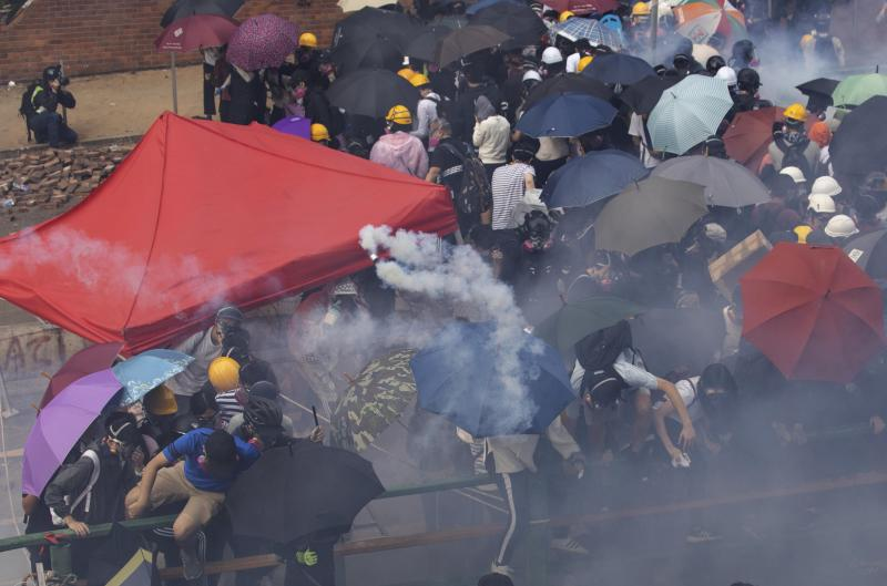 Protesters trying to leave the Hong Kong Polytechnic University scatter as police tear gas fills the air to keep them on the campus in Hong Kong on Monday, Nov. 18, 2019. (AP Photo/Ng Han Guan)