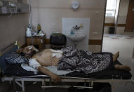 Mohammad Nassar, 31, rests at the Shifa hospital in Gaza City, Thursday, May 13, 2021, where he is receiving treatment for wounds caused by a May 12 Israeli strike that hit while he was driving a motorcycle. Just weeks ago, the Gaza Strip's feeble health care system was struggling with a runaway surge of coronavirus cases. Now doctors across the crowded coastal enclave are trying to keep up with a very different crisis: blast and shrapnel wounds, cuts and amputations. (AP Photo/Khalil Hamra)