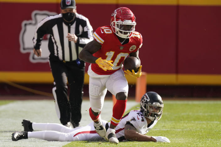 Kansas City Chiefs wide receiver Tyreek Hill runs down the sideline after evading a tackle by Atlanta Falcons A.J. Terrell during an NFL football game, Sunday, Dec. 27, 2020, in Kansas City. (AP Photo/Charlie Riedel)