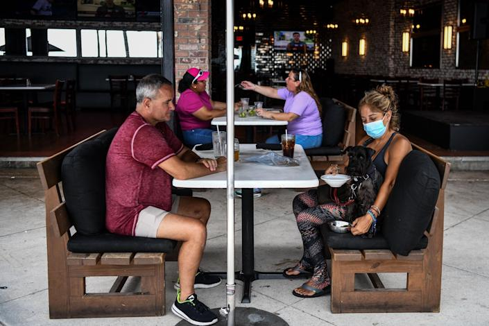 People eat outside a restaurant in Fort Lauderdale, Florida, on May 18, 2020.