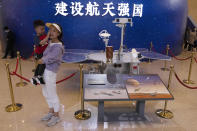 Visitors to an exhibition on China's space program pose for photos next to a life size model of the Chinese Mars rover Zhurong, named after the Chinese god of fire, at the National Museum in Beijing on Thursday, May 6, 2021. China has landed a spacecraft on Mars for the first time in the latest advance for its space program. The official Xinhua News Agency said Saturday, May 15, that the lander had touched down, citing the China National Space Administration. Chinese characters read: Build a Space Power. (AP Photo/Ng Han Guan)