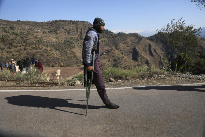 Mohammed Shokat, who lost his leg in cross0firing between India and Pakistan, walks with the help of a crutch in Poonch, India, Wednesday, Dec. 16, 2020. The terrain along the Line of Control, that for the past 73 years divided the region between the two nuclear-armed rivals of India and Pakistan, is tough and the life of civilians living in the area is even tougher, with them often caught in the line of fire. Over the last year, troops from the two sides have traded fire almost daily along the frontier, leaving dozens of civilians and soldiers dead. (AP Photo/Channi Anand)