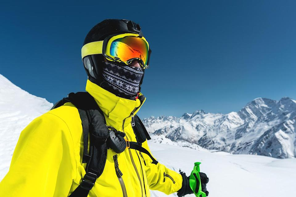Close-up portrait of a skier in a mask and helmet with a closed face against a background of snow-capped mountains and blue sky