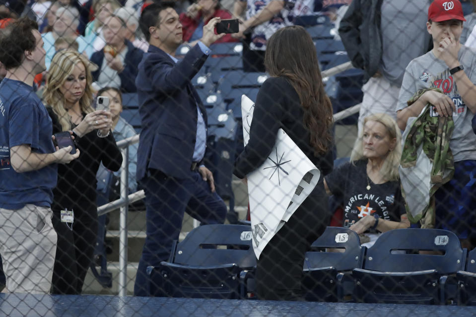 A ballpark official takes a sign from a fan before spring training baseball game between the Houston Astros and Washington Nationals on Saturday, Feb. 22, 2020, in West Palm Beach, Fla.